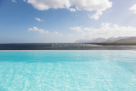 Sunny, tranquil infinity pool with ocean view under blue sky with cloudsの写真素材 [FYI02179100]