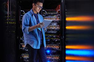 Focused male IT technician using digital tablet at panel in dark server roomの写真素材 [FYI02179116]