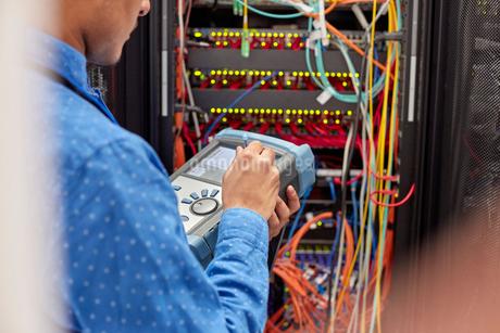 IT technician using fiber optic tester equipment in server roomの写真素材 [FYI02179127]