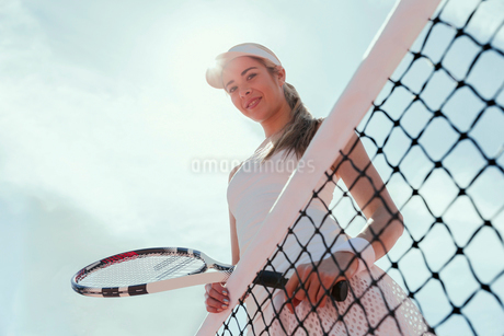Portrait smiling, confident female tennis player holding tennis racket at net below sunny skyの写真素材 [FYI02179132]
