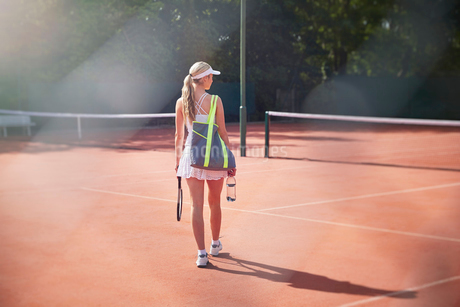 Young female tennis player walking with tennis racket, bag and water bottle on sunny clay tennis couの写真素材 [FYI02179146]