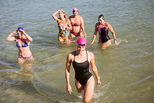 Overhead view female open water swimmers wading in sunny oceanの写真素材 [FYI02179147]