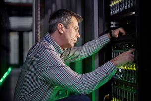 Focused male IT technician working at panel in dark server roomの写真素材 [FYI02179158]