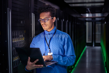 Focused male IT technician using laptop in dark server roomの写真素材 [FYI02179184]