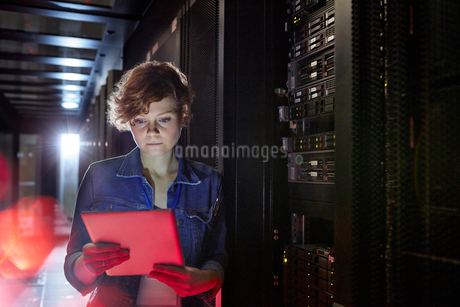 Focused female IT technician using digital tablet in server roomの写真素材 [FYI02179186]