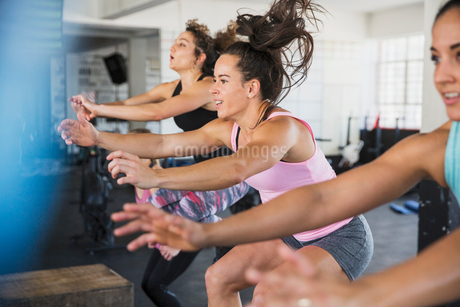 Energetic young women riding elliptical bikes in exercise classの写真素材 [FYI02179190]