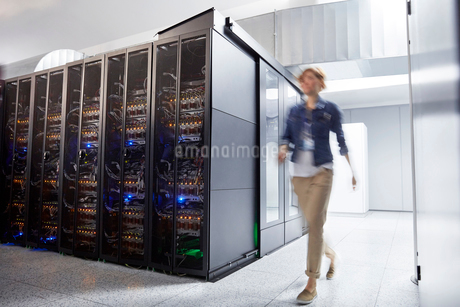 Female IT technician walking in server roomの写真素材 [FYI02179232]