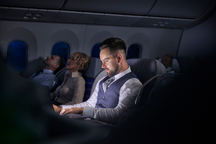 Businessman working on laptop on night airplaneの写真素材 [FYI02179233]