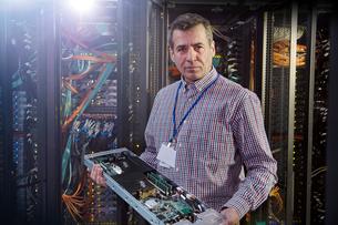 Portrait male IT technician holding panel in server roomの写真素材 [FYI02179251]