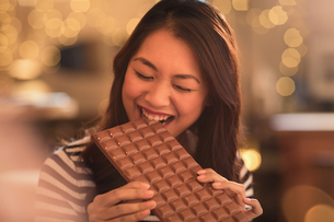 Woman with sweet tooth craving biting into large chocolate barの写真素材 [FYI02179262]