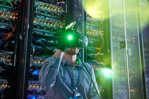 Male computer programmer using virtual reality simulator glasses and glowing glove in server roomの写真素材 [FYI02179266]