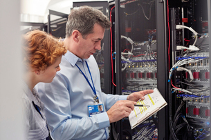 IT technicians with clipboard examining panel in server roomの写真素材 [FYI02179286]