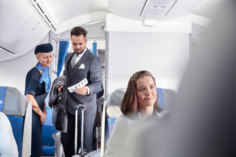 Flight attendant helping businessman with boarding pass on airplaneの写真素材 [FYI02179291]