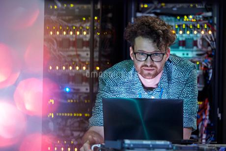 Focused male IT technician working at laptop in dark server roomの写真素材 [FYI02179334]