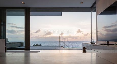 Home showcase living room and patio with tranquil sunset ocean viewの写真素材 [FYI02179342]