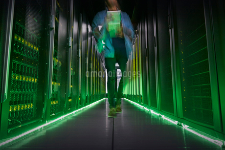 IT technician walking in dark, glowing server roomの写真素材 [FYI02179345]