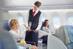 Flight attendant serving champagne to woman in first class on airplaneの写真素材 [FYI02179355]