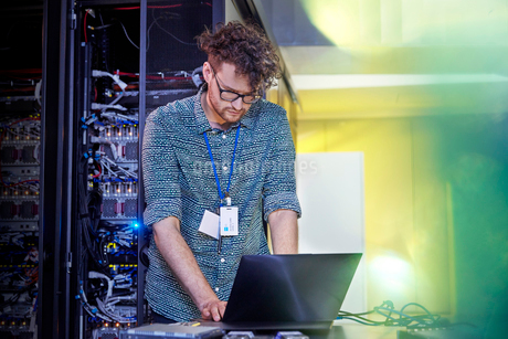 Male IT technician working at laptop in server roomの写真素材 [FYI02179367]