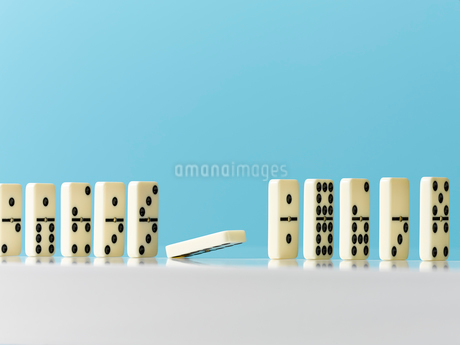 Domino falling in a row on blue backgroundの写真素材 [FYI02179370]