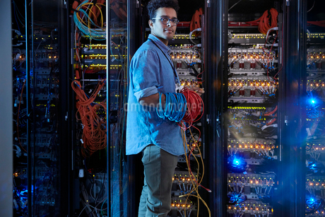 Portrait confident male IT technician holding cables in server roomの写真素材 [FYI02179373]