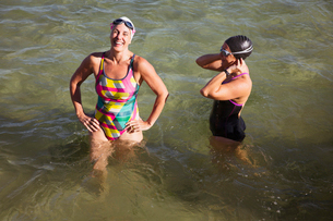 Laughing female open water swimmers wading in sunny oceanの写真素材 [FYI02179406]