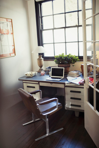 Laptop and paperwork on desk in home officeの写真素材 [FYI02179421]