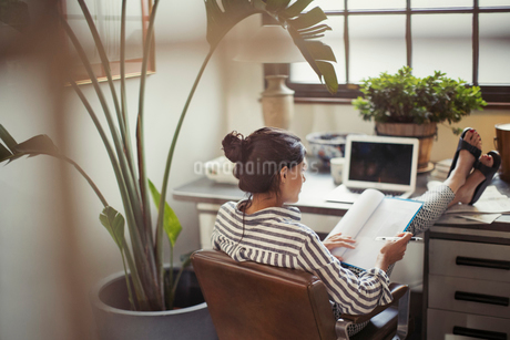 Businesswoman reading paperwork with feet up on deskの写真素材 [FYI02179430]