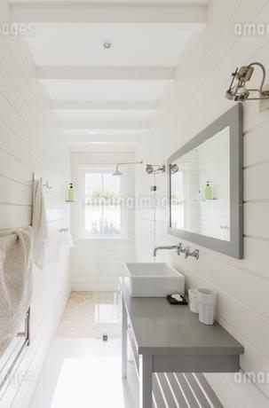 Long, sunny white modern luxury bathroomの写真素材 [FYI02179435]