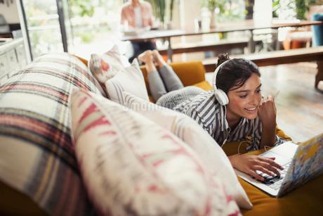 Smiling woman with headphones using laptop on sofaの写真素材 [FYI02179439]