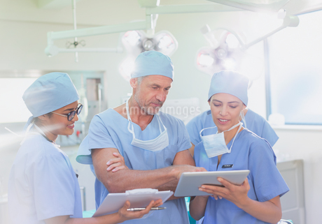 Surgeons and nurse using clipboard and digital tablet in operating roomの写真素材 [FYI02179441]