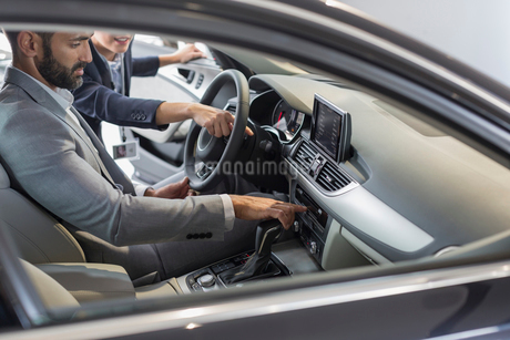 Car saleswoman pointing, explaining new car to male customer in driver's seatの写真素材 [FYI02179442]