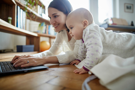 Baby daughter watching mother typing on laptop on floorの写真素材 [FYI02179447]