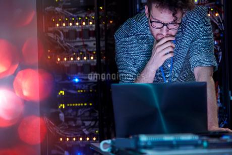Focused male IT technician working at laptop in dark server roomの写真素材 [FYI02179457]