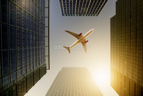 Airplane flying over highrise buildings, travel conceptの写真素材 [FYI02179461]