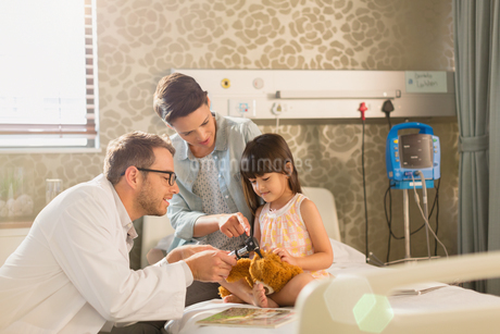 Male doctor using otoscope on teddy bear of girl patient in hospital roomの写真素材 [FYI02179465]