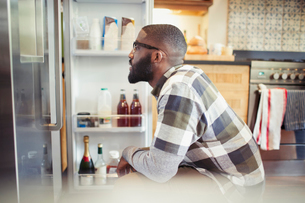 Hungry man peering into refrigerator in kitchenの写真素材 [FYI02179470]