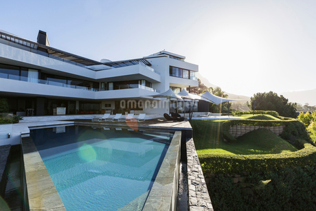 Sunny modern luxury home showcase exterior with infinity poolの写真素材 [FYI02179527]