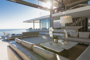 Sunny modern, luxury home showcase interior living room with ocean viewの写真素材 [FYI02179544]
