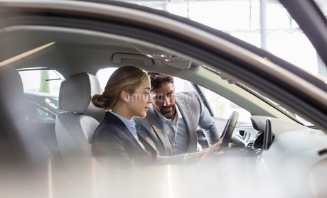 Car salesman showing new car to woman in driver's seat at car dealershipの写真素材 [FYI02179555]