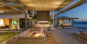 Illuminated modern, luxury home showcase interior living room open to patio at duskの写真素材 [FYI02179563]