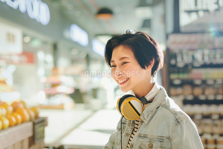 Smiling young woman with headphones grocery shopping in marketの写真素材 [FYI02179590]