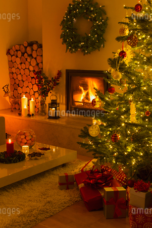 Ambient fireplace and candles illuminating living room with Christmas tree and decorationsの写真素材 [FYI02179593]