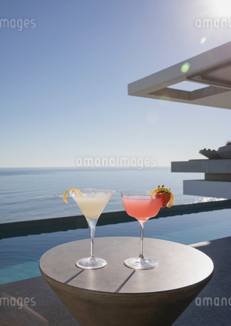 Cocktails in martini glasses on sunny luxury patio with ocean viewの写真素材 [FYI02179594]