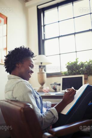 Smiling businesswoman reviewing paperwork at deskの写真素材 [FYI02179598]