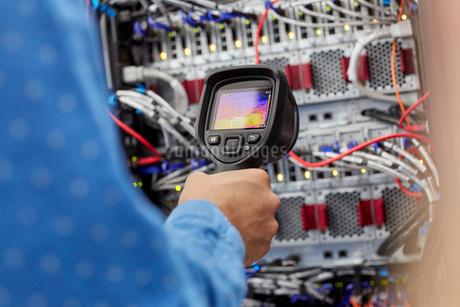 IT technician using diagnostic thermal imagining camera equipment in server roomの写真素材 [FYI02179600]