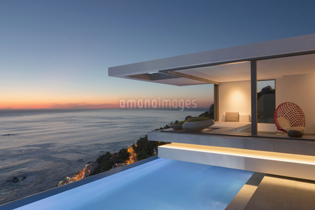 Illuminated modern, luxury home showcase exterior patio with lap pool and ocean view at twilightの写真素材 [FYI02179602]