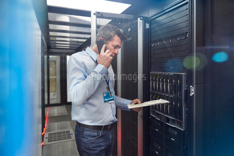 Male IT technician with clipboard talking on cell phone at panel in server roomの写真素材 [FYI02179606]