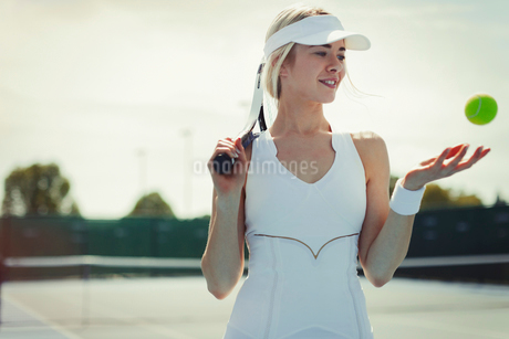 Smiling young female tennis player holding tennis racket and tennis ball on tennis courtの写真素材 [FYI02179612]