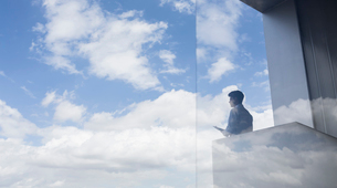 Pensive businessman standing on modern balcony looking at blue sky and cloudsの写真素材 [FYI02179616]