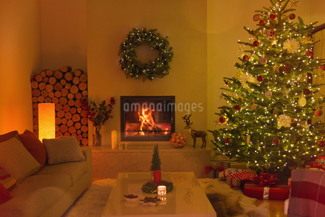 Ambient fireplace and candles in living room with Christmas treeの写真素材 [FYI02179634]